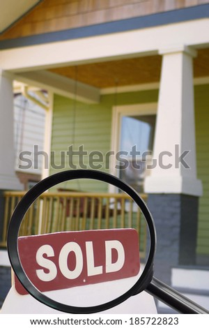 House for sale with sold sign and magnifying glass - stock photo