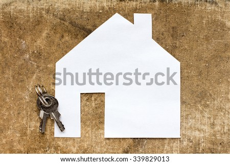 House icon and keys on dirty canvas background - stock photo