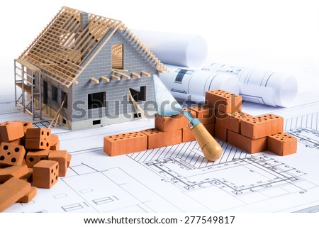 house in construction - project with brick and blueprint - stock photo