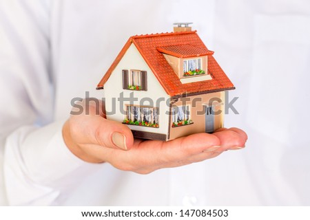 house in human hands on a white background - stock photo