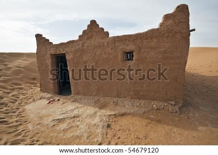 House in Sahara desert in Morocco. Horizontal shot. - stock photo