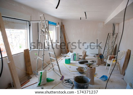 House indoor improvements in a messy room construction with plaster tools and ladder - stock photo