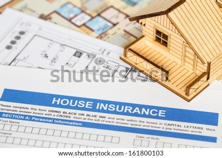 House insurance application with model house and construction plan - stock photo