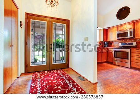 House interior. Entrance hallway with glass door, hardwood floor and bright red rug. View of kitchen room with orange cabinets and steel stove - stock photo