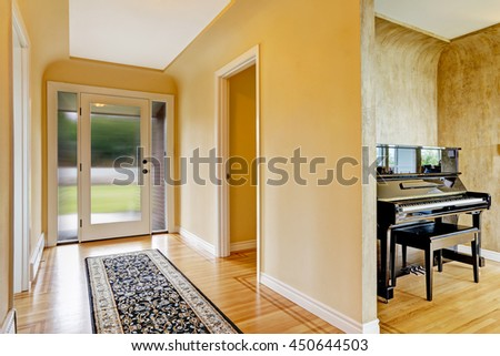 House interior. Entrance hallway with glass door, hardwood floor and  rug. View of piano - stock photo