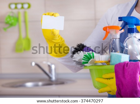 House keeper holding basin full of cleaning supplies and showing business card in front of clean kitchen - stock photo