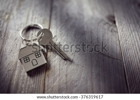 House key on a house shaped keychain resting on wooden floorboards concept for real estate, moving home or renting property - stock photo
