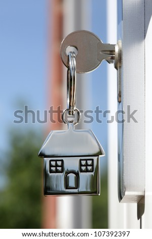 House key on a house shaped silver keyring in the lock of a door - stock photo