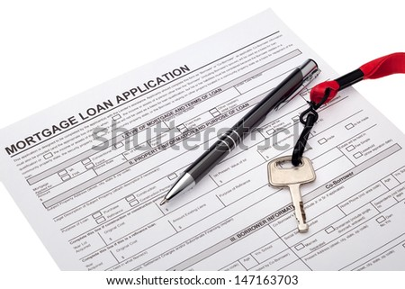 House key with mortgage loan application - stock photo
