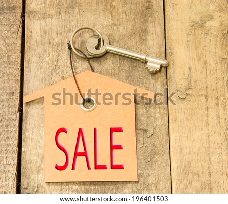 House Key with Sale tag  on a background of wooden. - stock photo