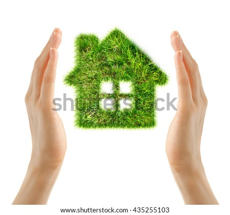 House made of green grass in female hands - stock photo