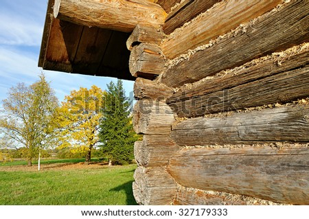 House made of logs with moss insulation in the cracks in traditional Russian style on the background of autumn trees - rural landscape - stock photo