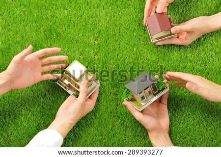 House miniature and hand,Green turf - stock photo