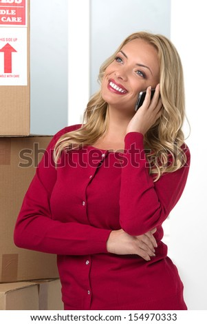 House moving. Cheerful middle-aged woman standing near the cardboard box stack and talking on the mobile phone - stock photo