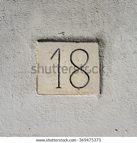House number eighteen engraved in a concrete wall - stock photo
