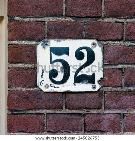 house number fifty two. Black numerals on a white plate - stock photo