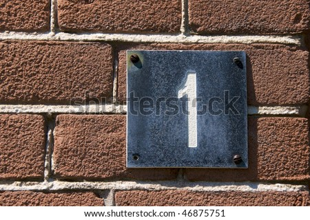 House number, No. 1 on a red brick wall - stock photo