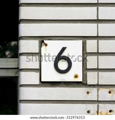 house number 6 on a white brick wall. - stock photo