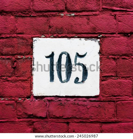 House number one hundred and five, carved in stone - stock photo