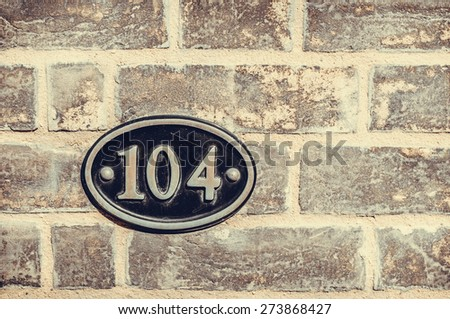 House number one hundred and four engraved in a black metal plate and brick wall - stock photo