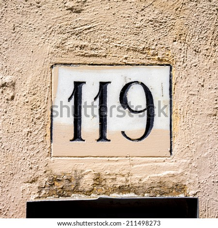 House number one hundred and nineteen, on a peach colored stucco wall. - stock photo