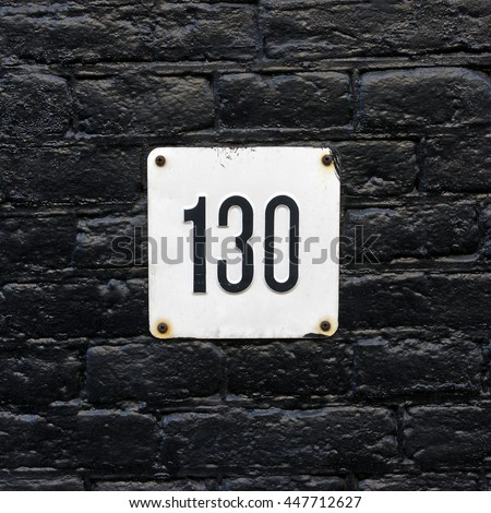 House number one hundred and thirty (130) embossed in a metal plate - stock photo
