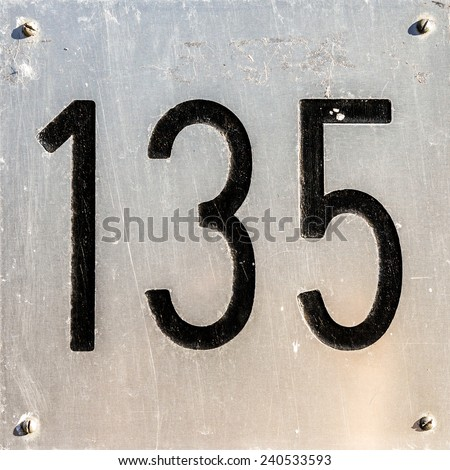 House number one hundred and thirty five, engraved in an aluminum plate. - stock photo
