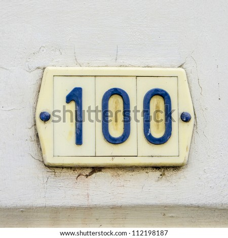 house number one hundred  made of plastic. Blue lettering on yellowish background. - stock photo