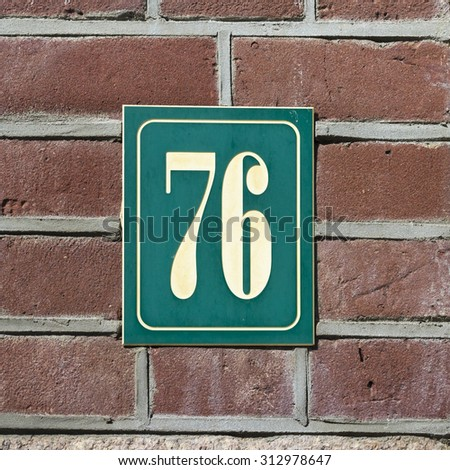 House number seventy six engraved in a plastic plate. - stock photo