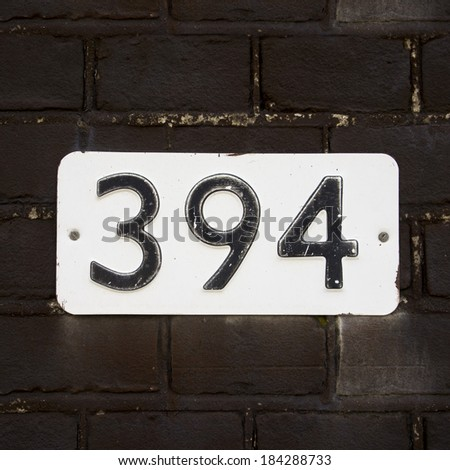 house number three hundred and ninety four, embossed in a metal plate. - stock photo