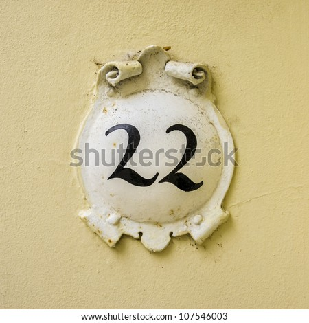 house number twenty-two on a round plate surrounded by curly ornaments - stock photo
