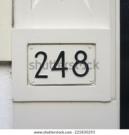 house number two hundred and forty-eight embossed in a metal placard. Painted over in black. - stock photo