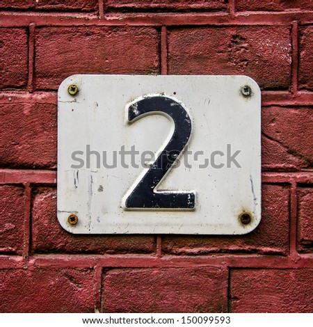 House number two on a red brick wall - stock photo