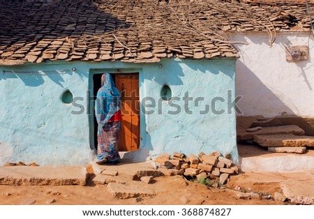 House of poor family and indian woman standing at the door of traditional style home, India.  - stock photo
