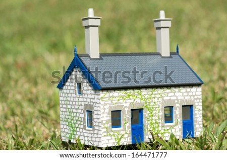 House on green grass. Concept photo of Real estate market bubble , booming, rent, money,price, grid, home, house, housing, industry and subprime mortgage crisis. (Copy Space) - stock photo