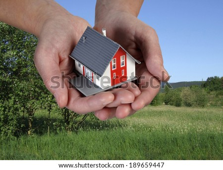House on hands in front of a green landscape. - stock photo