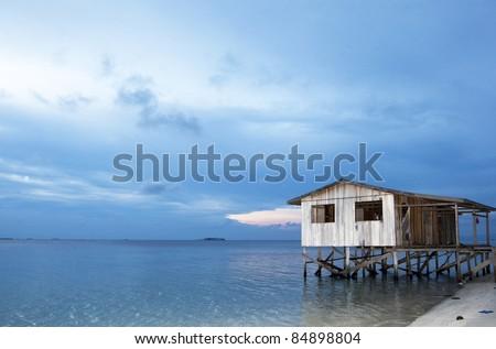 house on stilts on the sea at dusk, beachside, on island off Borneo Island. - stock photo