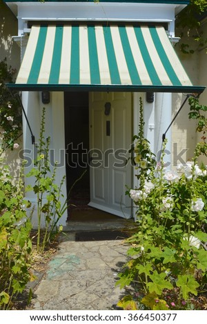 House open door with sun blind and Hollyhock flowers. - stock photo
