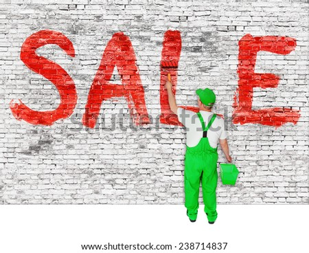 House painter announces sale on white brick wall - stock photo