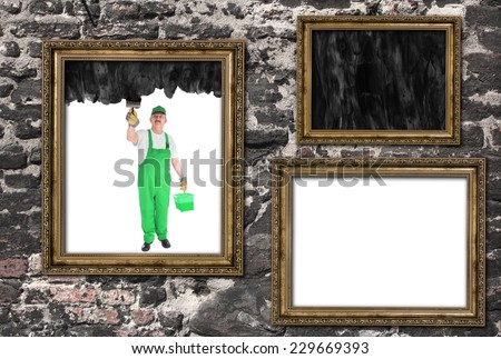 House painter covers inside of three frames on black - stock photo