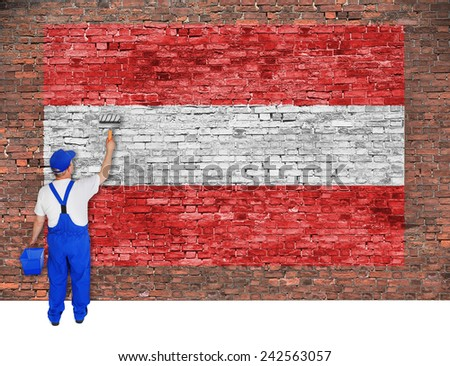 House painter covers old brick wall with flag of Austria - stock photo