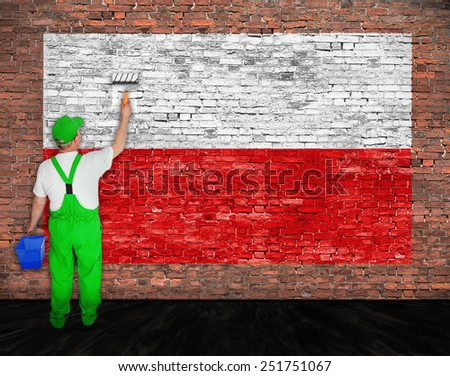 House painter paints flag of Poland on old brick wall - stock photo