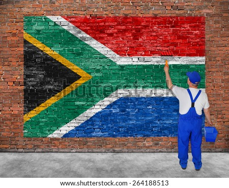 House painter paints flag of Republic of South Africa on old brick wall - stock photo