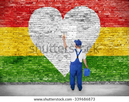 House painter paints heart symbol on Reggae flag - stock photo