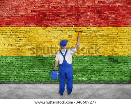 House painter paints Reggae flag on old brick wall - stock photo