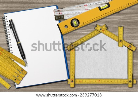 House Project - Yellow Wooden Meter. House project concept. Wooden meter ruler in the shape of house with pencil, empty notebook, two meter tools and spirit level on a wooden desk - stock photo