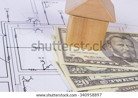 House shape made of wooden blocks and currencies dollar lying on electrical construction drawings of house, concept of building house, drawing for projects - stock photo