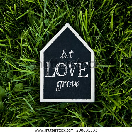 """house shaped chalk board saying  """"let love grow""""  on the grass background - stock photo"""