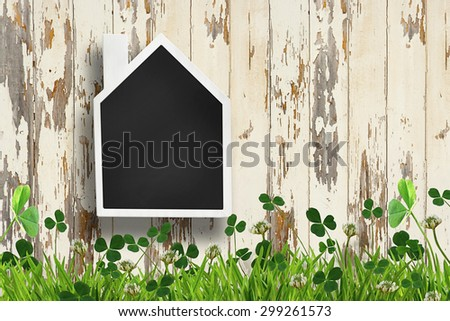House shaped chalkboard on wooden plank background - stock photo