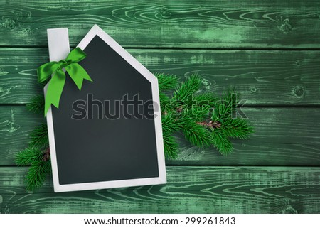 House shaped chalkboard with Christmas background - stock photo
